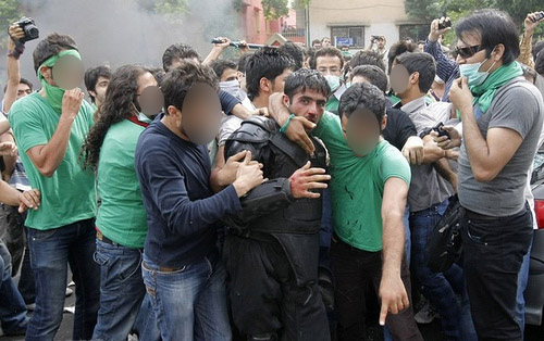 Protesters assist a riot policeman in distress in Tehran Protesters assist a riot policeman in distress in Tehran